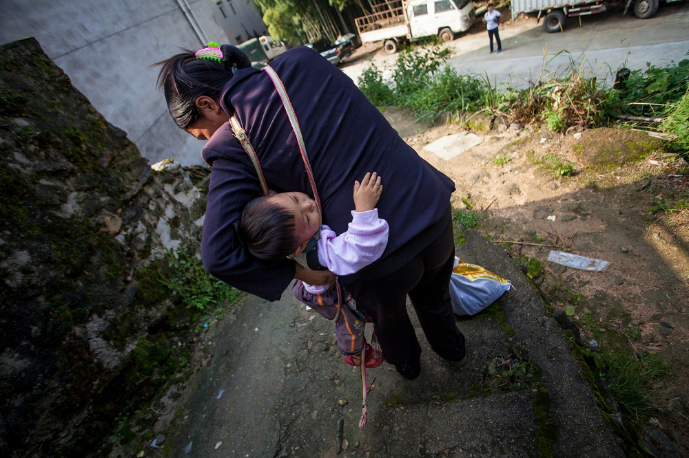 Li Xiaowei carries her daughter, Huang Qinqin, as she goes down the hill to the village to do business.