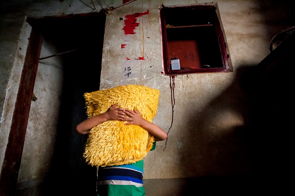The Huang's young son, Huang Chaoshuai, plays with a yellow pillow that has become his version of a security blanket.
