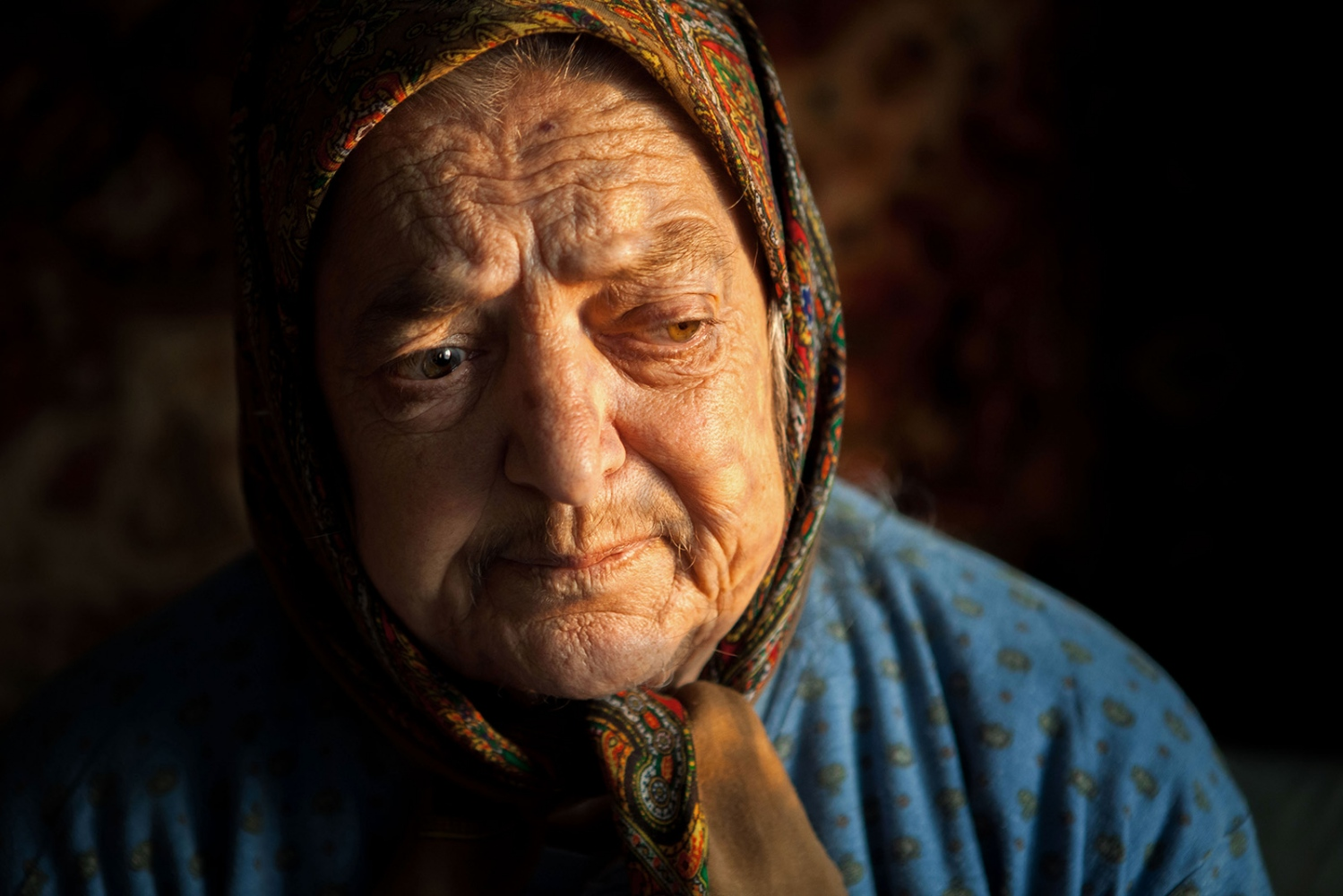 "Pasha, an elderly woman living in rural Moldova, in the village of Vadeni, sits in the warm evening sunlight, as we talk about her life in the single, small room she inhabits everyday. Pasha can no longer walk due to extreme leg pain and was confined to her one room in the small separate house she and her sister, Ana, share. She is frequently moved to tears as we discuss her exile to Kazahkstan, ""[The night we were deported] …they took us to the police station in Floresti (a nearby town to Vadeni, Pasha's home village, in the Northern region of Moldova). From there, they put us in a cattle car on a train. There was nothing inside. No toilet, no food, nothing, and thus we travelled for 2 months … some people died [during the journey], inside the train cars."" – Pasha Graur Across the former Soviet Union, millions of people were forcibly deported over the course of decades to the Eastern Soviet States of Kazakhstan and Siberia. This event is one of the longest and deadliest government campaigns in history. In Moldova, hundreds of thousands of people were deported, from 1939 to the early 1950's. The wave of deportations targeted intellectuals, large landowners, dissidents and, at times, regular people who had done nothing to promote attack. Those who were deported had their land and homes taken from them and redistributed to the Soviet state and were deemed ""Enemies of the People"" and were systematically shamed and silenced over the course of decades. Only recently has Moldova been willing to listen to the stories of deportees and try to understand the dark history of their country."