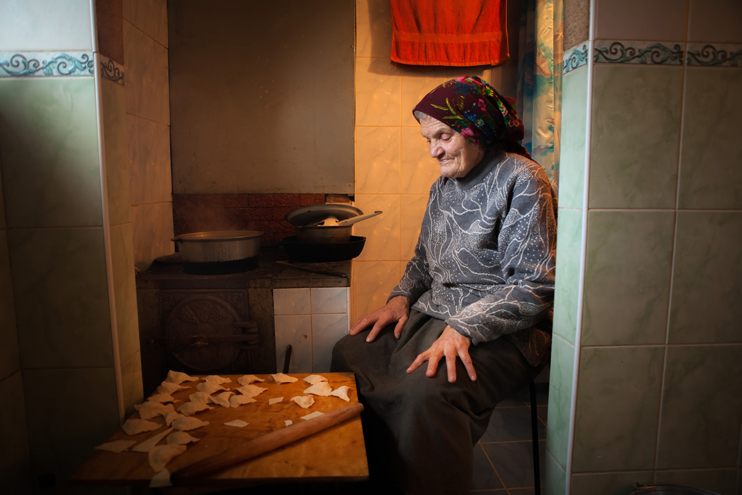"Ana, Pasha's sister sits in the family kitchen as she prepares coltunasi, a traditional Moldovan dumpling, in the dead of frozen January. I see that she is staring quietly into nothing and I ask her what she is thinking about. She responds simply with, ""My sister, my daughter in Italy, my brother, [Leonid] who died. I am remembering my family."" Ana is the pillar of strength of her home. Always busy, she rarely takes a moment to sit and rest. As I have gotten to know her better it becomes clear how she uses her work as a means to survive her past. The moment she stops working, the memory flood in and, at times, a quiet melancholy will cross her face. As we talk more and she laments her age, I joke that she is still young and active. We laugh together and she later says, ""I don't know if I was ever young. My childhood was so sad, I don't think I was a child then."""