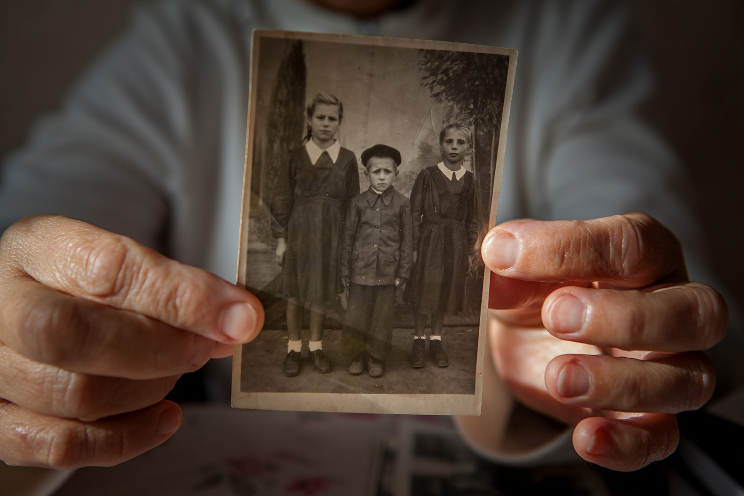 Ion's wife, Nina, who was also a deportee born in Siberia, holds up a photo of Ion and his siblings that was taken in Siberia at the time of his deportation. While Ion and his siblings successfully returned to Moldova, not all of his family was so lucky. Shortly before their return a younger brother of theirs died due to the extreme cold of Siberia and frailty of body that was a reality for all deportees at the time. Frequently, deportees talk about the small portions of bread and basic food they were given for their days' work, as well as the small salaries. It was not uncommon for deportees to sell precious family heirlooms for a bucket of potatoes or the like.