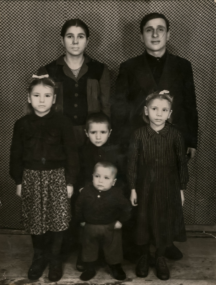 "Ion Postica keeps a photo, taken in Siberia, of his family after they were deported. Ion's brother, Andrei (pictured lower center), echoes Ion's sentiment that their parents were the ones that bore the greatest burden of the deportations during their time in Siberia. ""I was little. I would play all day long. Our parents were the ones who endured [the hardship]… I didn't feel the burden of my parents' problems, they endured them all by themselves."" - Andrei"