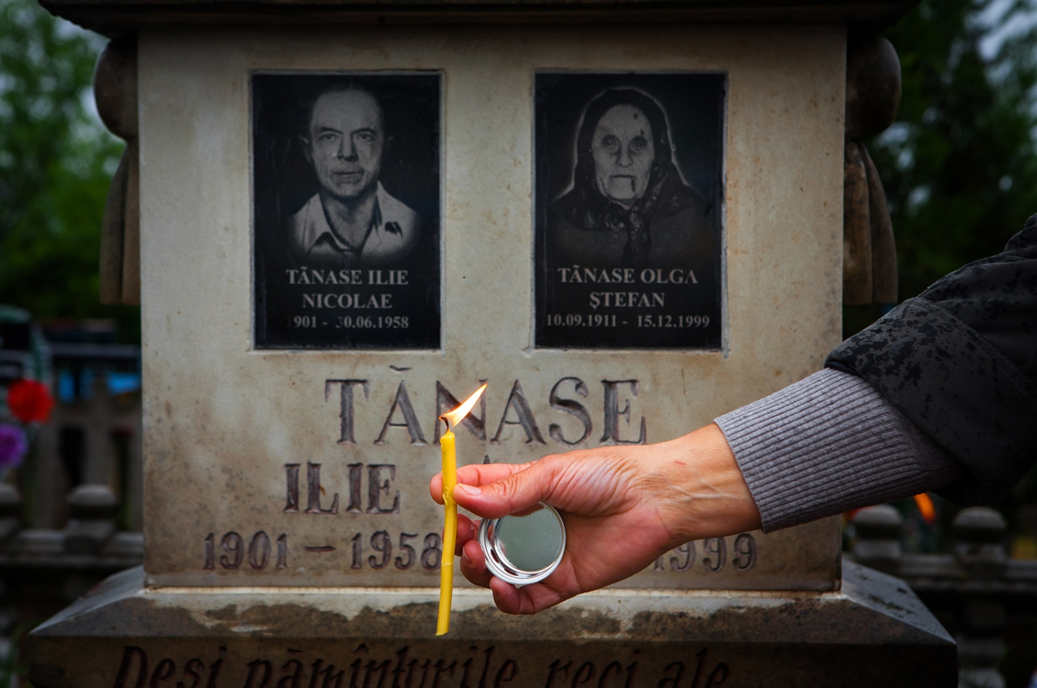 "Nina puts a candle in the earth in front of her parent's gravesite for pastele blajinilor, a part of Easter in Moldova where families go to visit their relatives' gravesites and give offerings and pray. Pictured above are her father, Nicolae, and her mother, Olga. Nina remembers, ""After Stalin died, my father was freed. He returned to Moldova and started looking for my mother. He sent a letter to Moscow, in the Soviet Union and asked where my mother was - where he could look for her so they could reunite as a family, but he had no luck… it took too long to get the legal forms. However, he found out where mother was from relatives and wrote to them asking if he could to go there. And so he went to my mother and found her where she was living. Thus, the family was reunited… [After my mother and father were reunited] another three children were born, (including Nina), but my father longed to return to Moldova and when mother and the rest of the family was allowed to go back… father got sick and died in Siberia… [When my parents were reunited,my father had] said to [my mother], 'You'll remain by my side until my last breath. I'm so sorry that you have suffered so much because of me. I'm very, very sorry. And the children must have suffered too. I regret to put you through all this. You go back home, to Moldova. You have no place [in Moldova] to go. You have no house… but you are strong. You'll survive and you'll take the children home.' He wanted very badly that mother should return with us to Moldova - to bring us all back. Mother says that she granted his last wish to bring their children home."" - Nina"