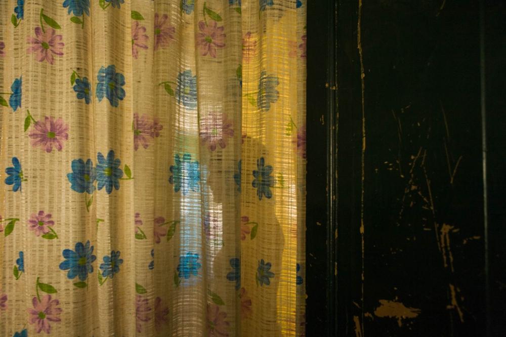 ·Amapola talking to her brother as seen through a curtain that separates the living room from her fathe´s room. As the only woman in the house, she is a key element for the sanity of the family. April 22nd, 2009. // · Amapola platicando con su hermano en la sala. Una cortina separa la sala del cuarto de su padre, Charlie. Siendo la unica mujer en la casa, ella ha servido una funcion clave en la sanidad de la famila. 22 de abril, 2009