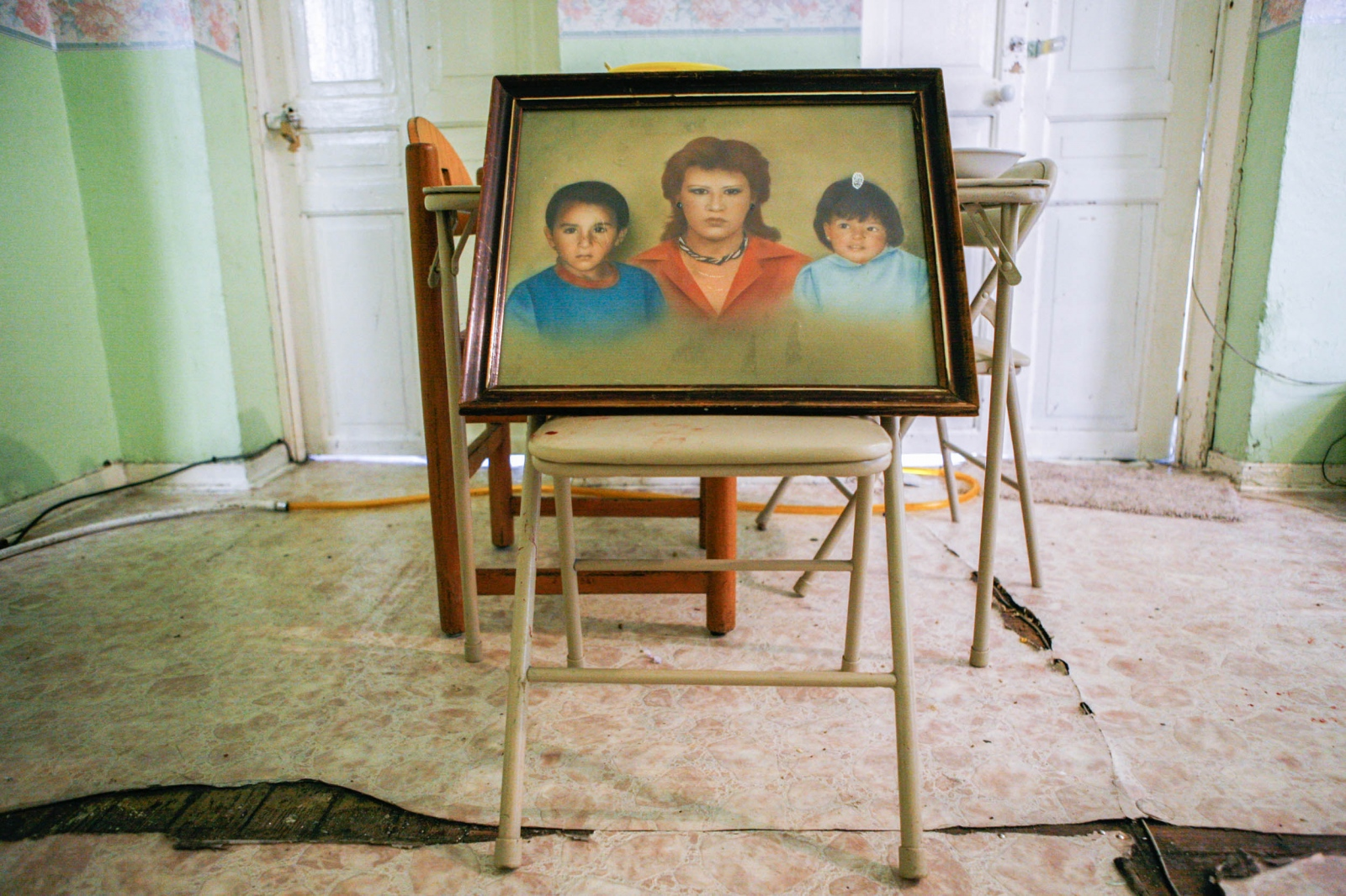 · Portrait of Jackeline and her two kids in the apartment which they resided for over a decade. The same apartment gave refuge to Lalo -the boy in the portrait- and his family for some time before he got divorced and Silvia moved to the rooftop with her three kids to live on a 1.5m x 1.5m room. 7 de julio de 2009.  // · Retrato de Jacqueline y sus dos hijos en el departamento que habitaron durante una década, mismo que más tarde albergó a la familia de Lalo —el niño en el retrato— por una temporada antes de que se divorciara de Silvia y que ella se mudara a a la azotea con sus tres hijos para vivir en un cuarto de 1.5m x 1.5 m. July 7th, 2009.