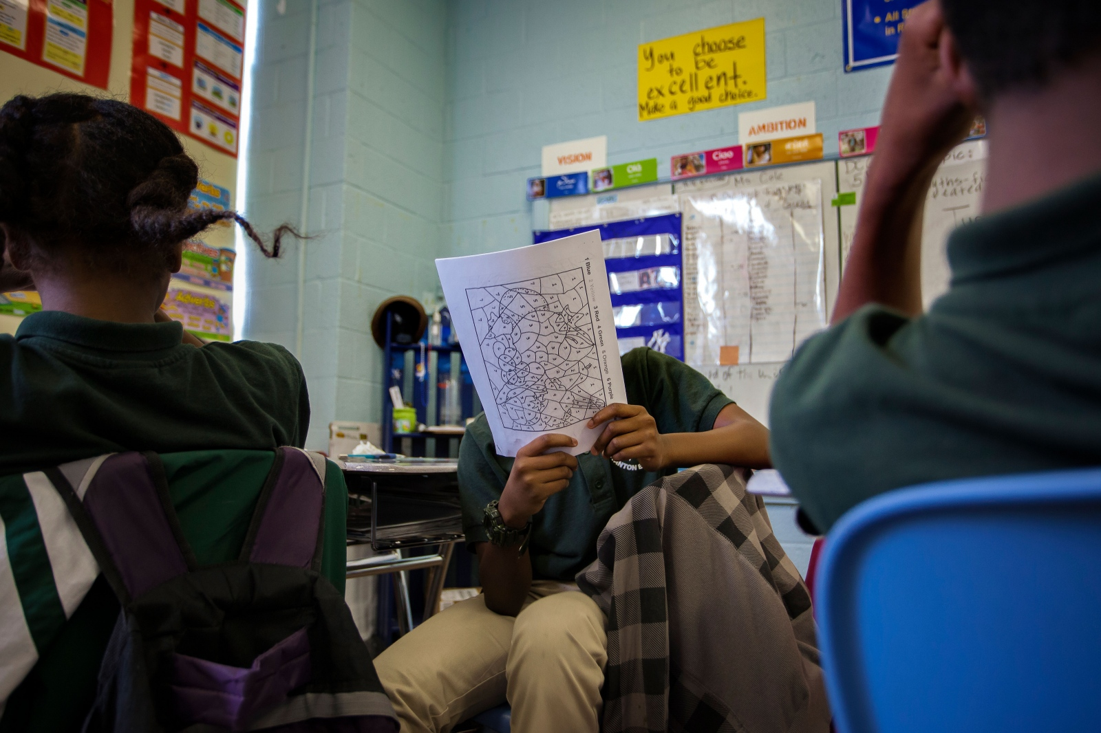 Students go over homework together in math class. Their teacher asks the answers to the questions and the students are asked to quietly raise their hands to respond. However, the rambunctious young kids often yell out the answers in excitement.