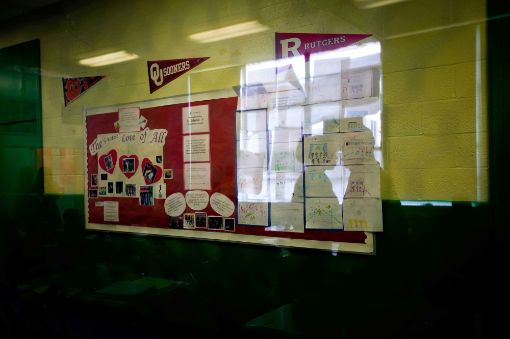 A fifth grade math class is reflected in the window look out into the hallway of Stanton Elementary. The school billboard outlines the month's learning theme.