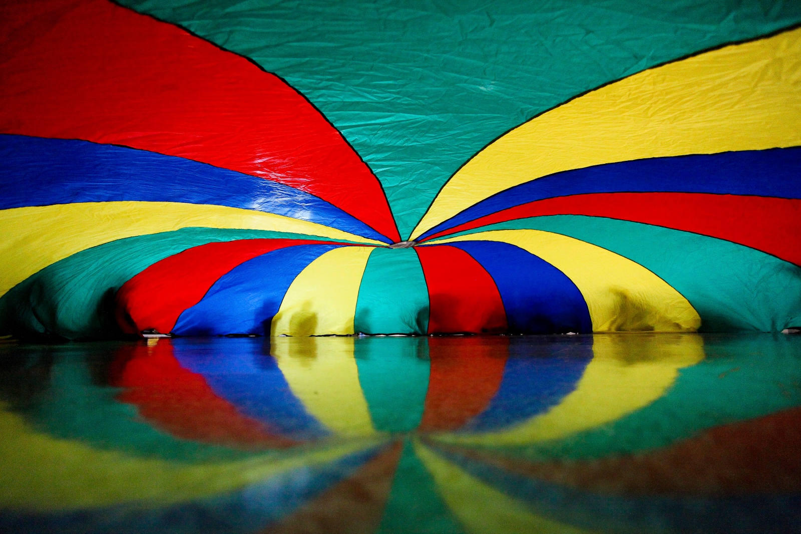 Students play with a parachute during gym class. Their laughter fills the gymnasium as their teacher educates them on the importance of teamwork.