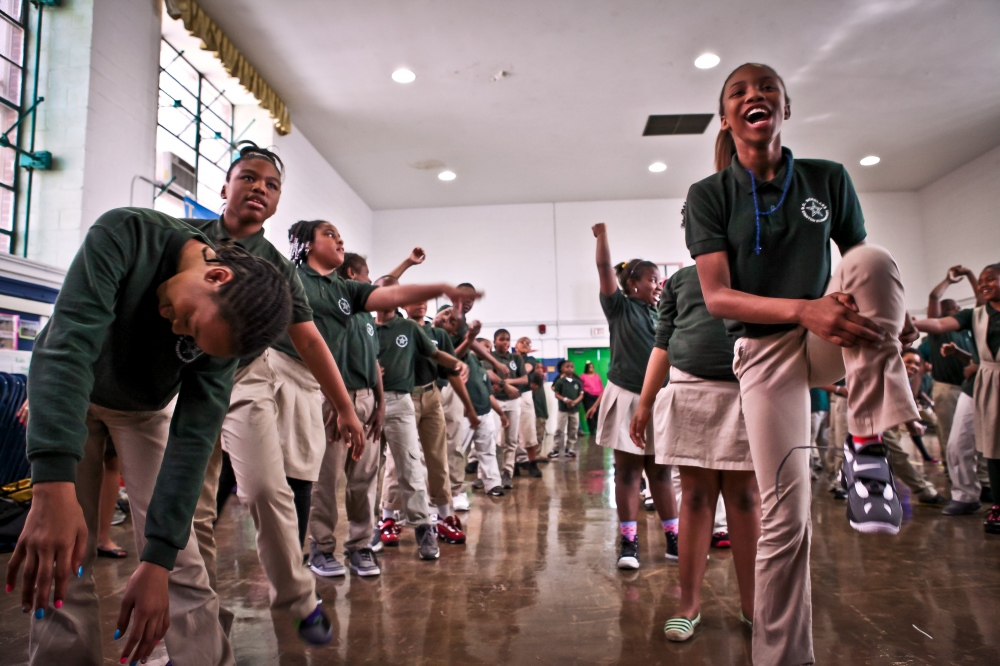 Students practice a dance that emphasizes the importance of learning at an end of the year celebration.