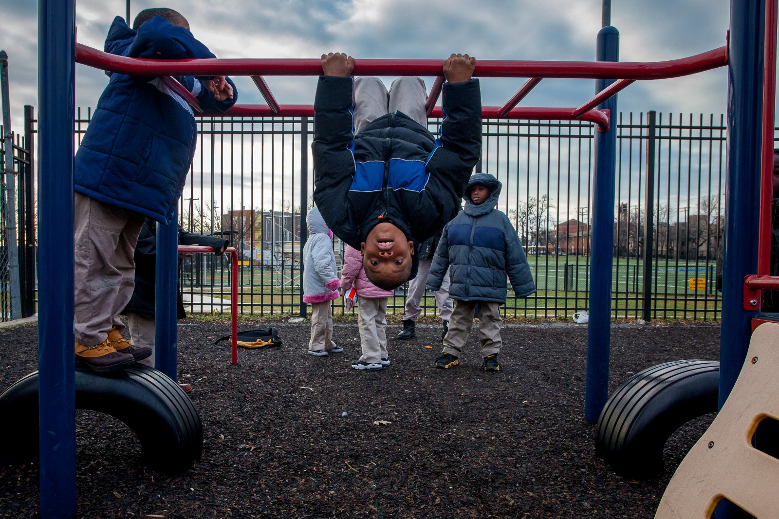 Students line up to flip off of the monkey bars during recess. Young kids in the Anacostia area are full of energy and athleticism.