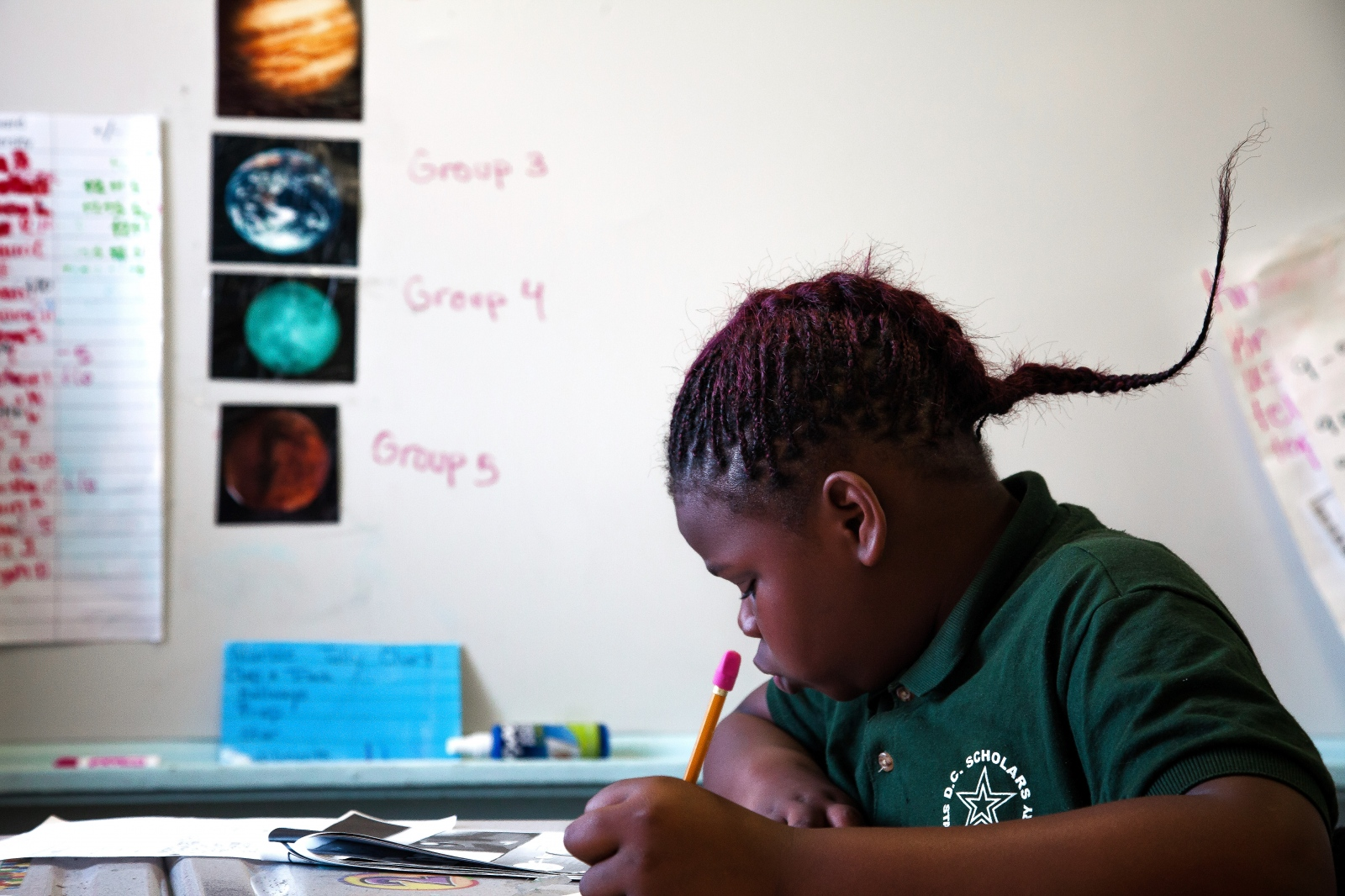 A student sits at her desk and works on homework during class time.