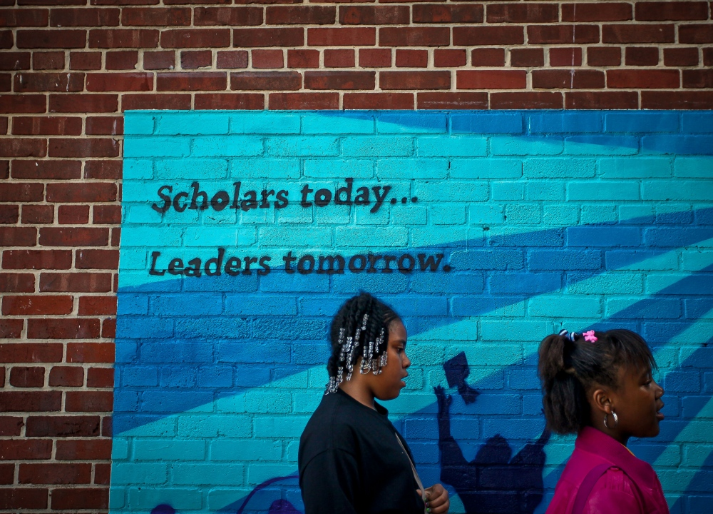 Stanton Elementary Students line up to go to school early in the morning. One of the school's mottos is painted on the brick wall.