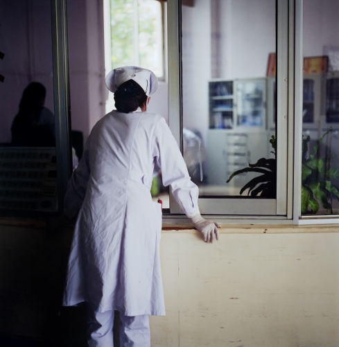 A nurse waits for information in a small city hospital in the Lijiang, China.