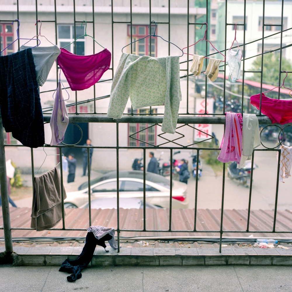 The clothes of family members visiting their loved ones hang on the bars of a small city hospital in the Jiangxi province of China.