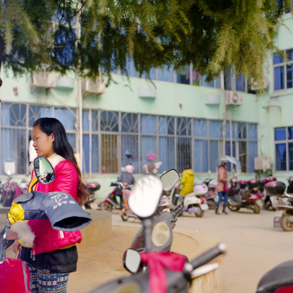 A woman waits in the parking lot of a small city hospital in the Jiangxi province in China.