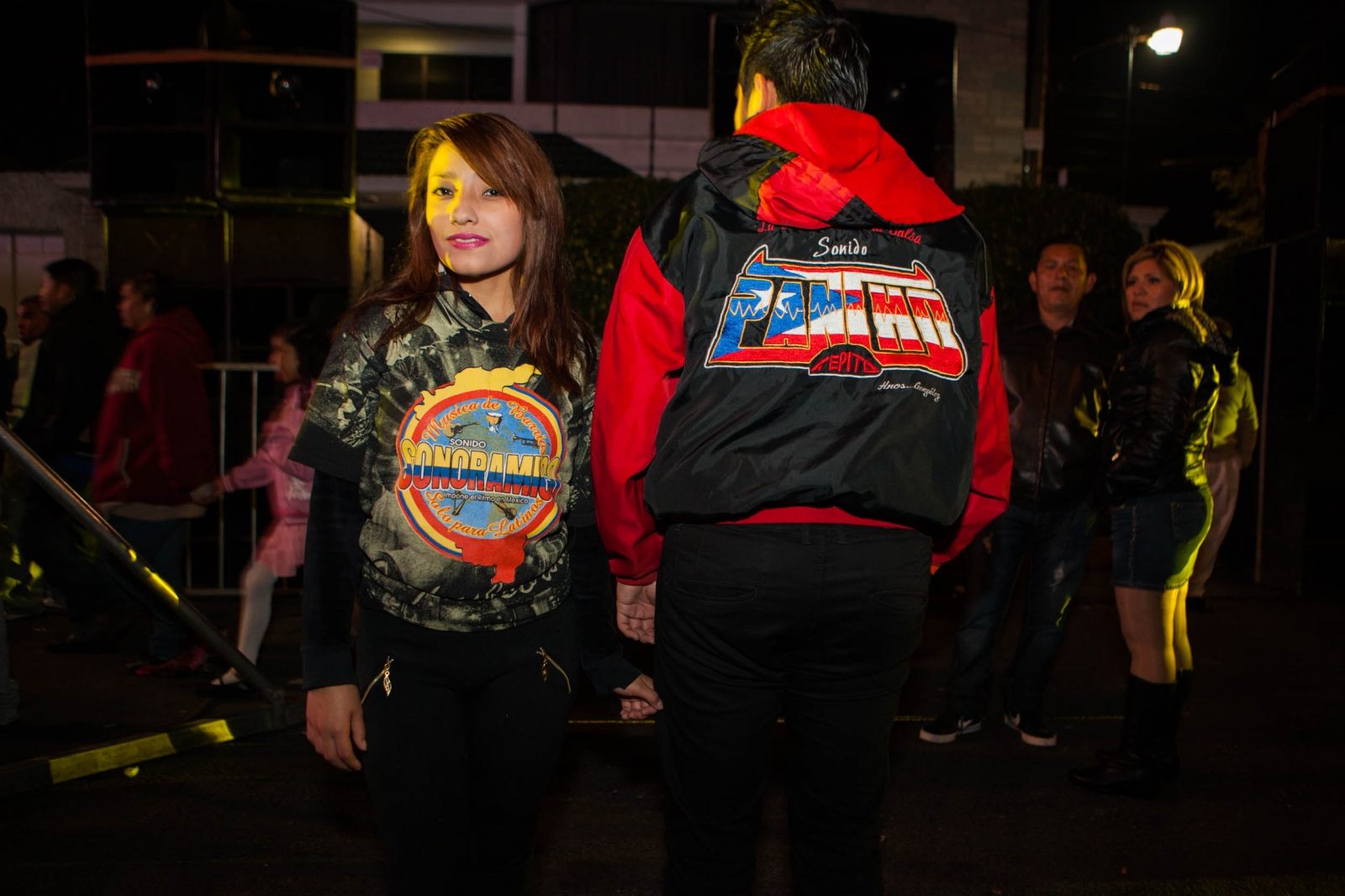 ·Couple wearing jackets with the logo of two of the most famous sonideros in Mexico City and who were playing that same night, Sonido Pancho from Tepito and Sonido Sonoramico from Peñon de los Baños, in the Bosques de Aragon neighborhood anniversary which lasts for two nights. Aragón, Mexico City. February, 2015 // · Pareja vistiendo chamarras de dos de los sonideros más populares en la Ciudad de México, ambos presentes en la tocada de esa noche, en el aniversario del barrio Bosques de Aragon, Sonido Pancho de Tepito y Sonido Sonoramico del Peñon de los Baños. Aragón, Mexico D.F. Febrero, 2015