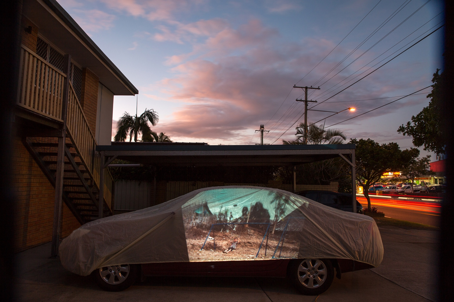 A projection of a boy on a swing on a playground erected by NGO 'Right to Play' in the refugee camp of Mae La on the Thai Burma Border. This image has been projected onto a driveway in Brisbane, Australia where a refugee family now resides.  QUEENSLAND, AUSTRALIA – July 2015.