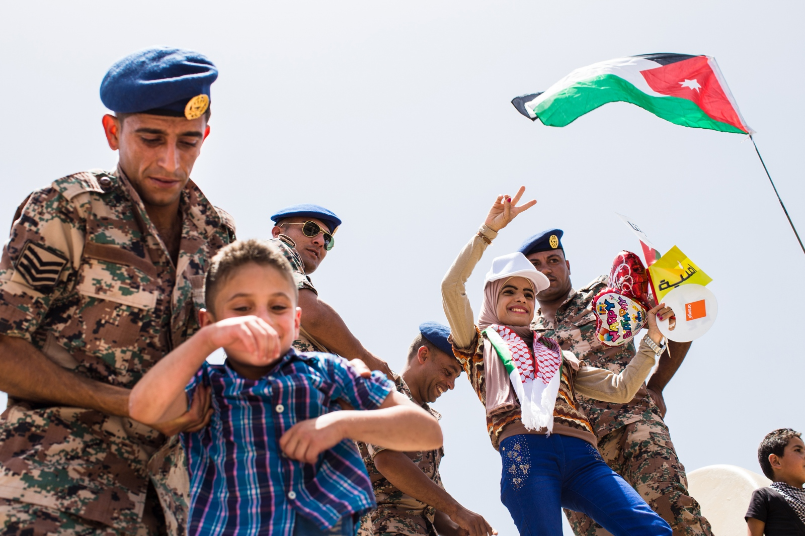 A Jordanian soldier helps a boy get on top of a tank for a photo, while another woman poses with soldiers. Large celebrations and festivals were held in Amman, Jordan to mark the centennial of the Great Arab Revolt on June 3, 2016.