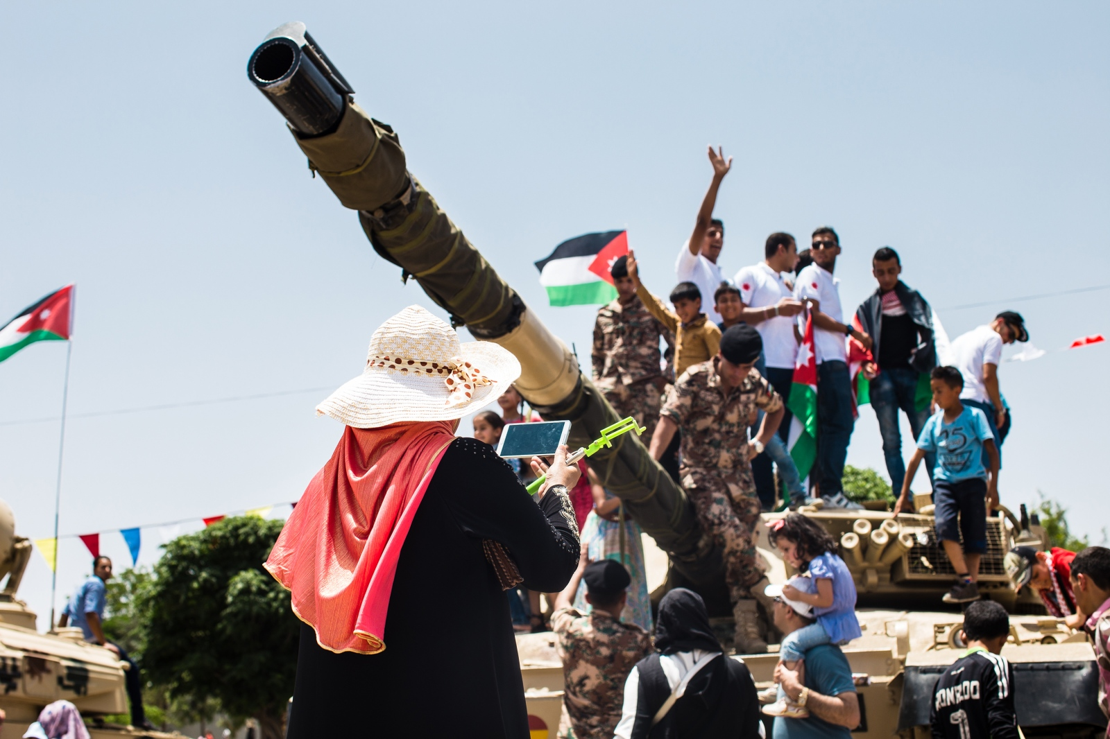 A Jordanian woman takes photos of family members and soldiers posing atop a tank at a celebration of the centennial of the Great Arab Revolt in Amman, Jordan on June 3, 2016.