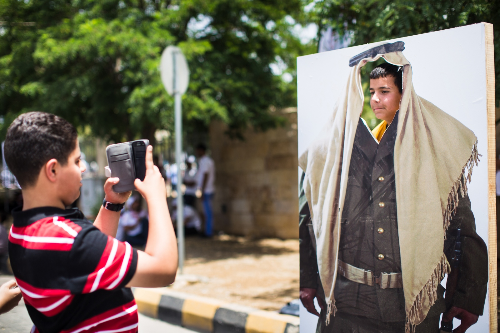 Two brothers take photos of each other in a face cutout of a bedouin soldier at a celebration for the 100th anniversary of the Great Arab Revolt in Amman, Jordan, on June 3, 2016.