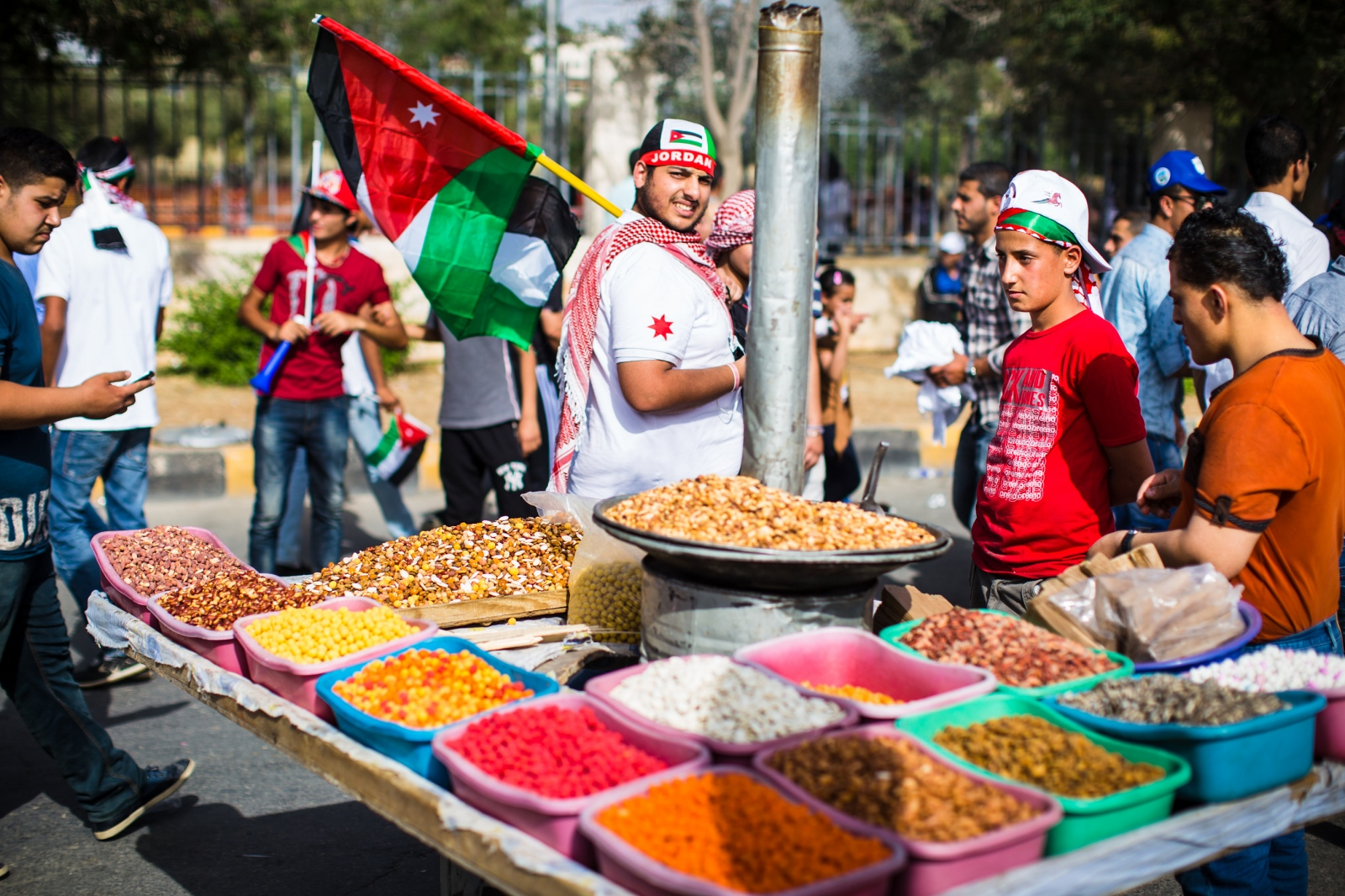 A Jordanian boy sells roasted nuts on the street outside King Hussein Park in Amman, Jordan, as crowds gathered to watch an air show and celebrate the 100th anniversary of the Great Arab Revolt on June 3, 2016.