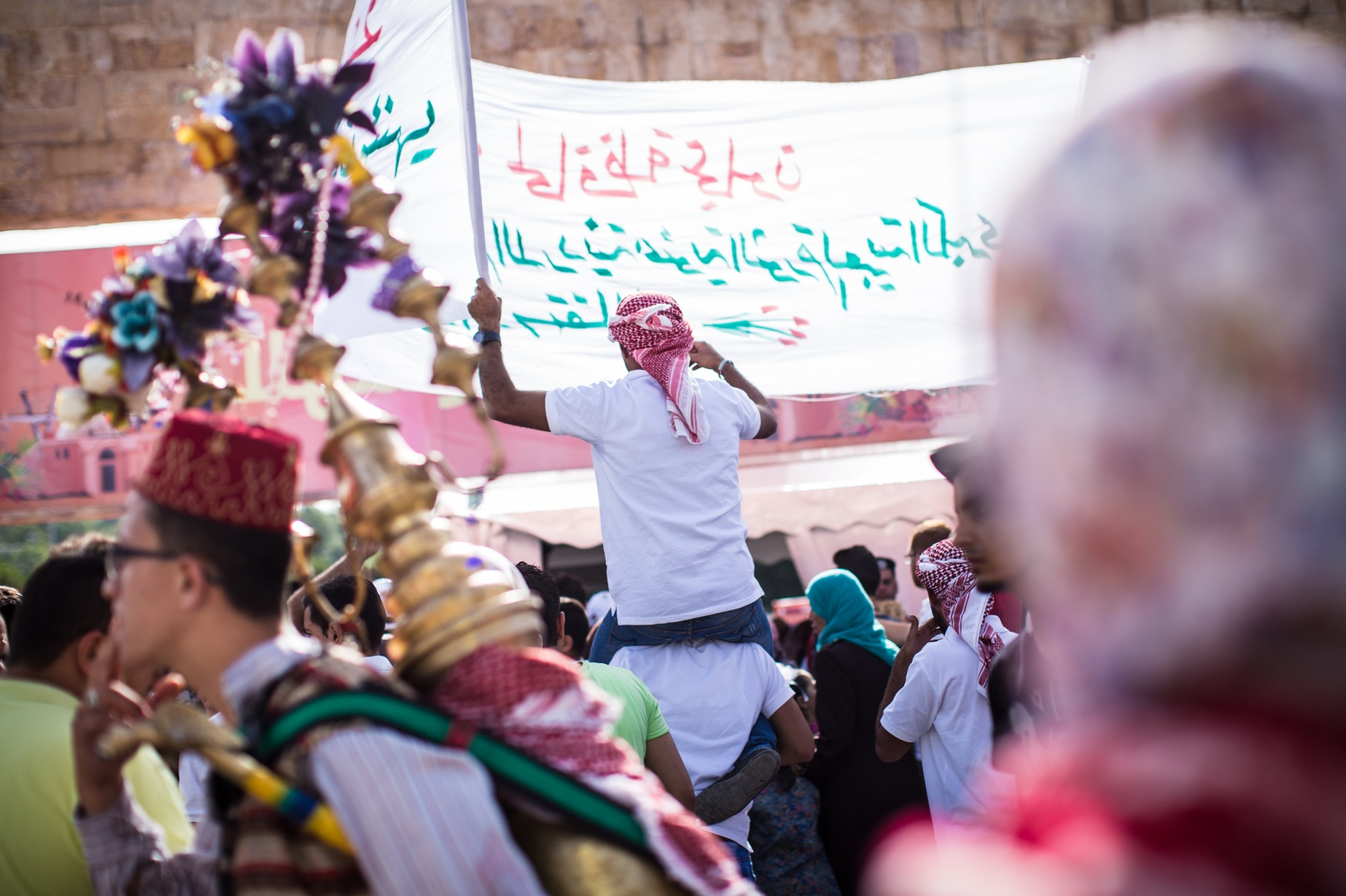 A parade chanting slogans in support of King Abdullah II passes through the crowd outside King Hussein Park in Amman, Jordan, as people gathered to celebrate the 100th anniversary of the Great Arab Revolt on June 3, 2016.