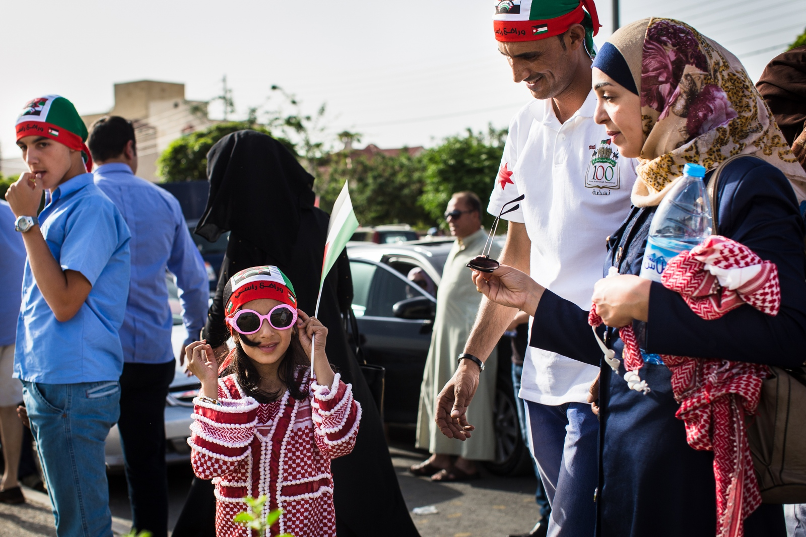 A young Jordanian girl, wearing a dress made out of a traditional kuffiyeh, tries on her pink sunglasses as she and her parents head to a festival celebrating the 100th anniversary of the Great Arab Revolt in Amman, Jordan, on June 3, 2016.