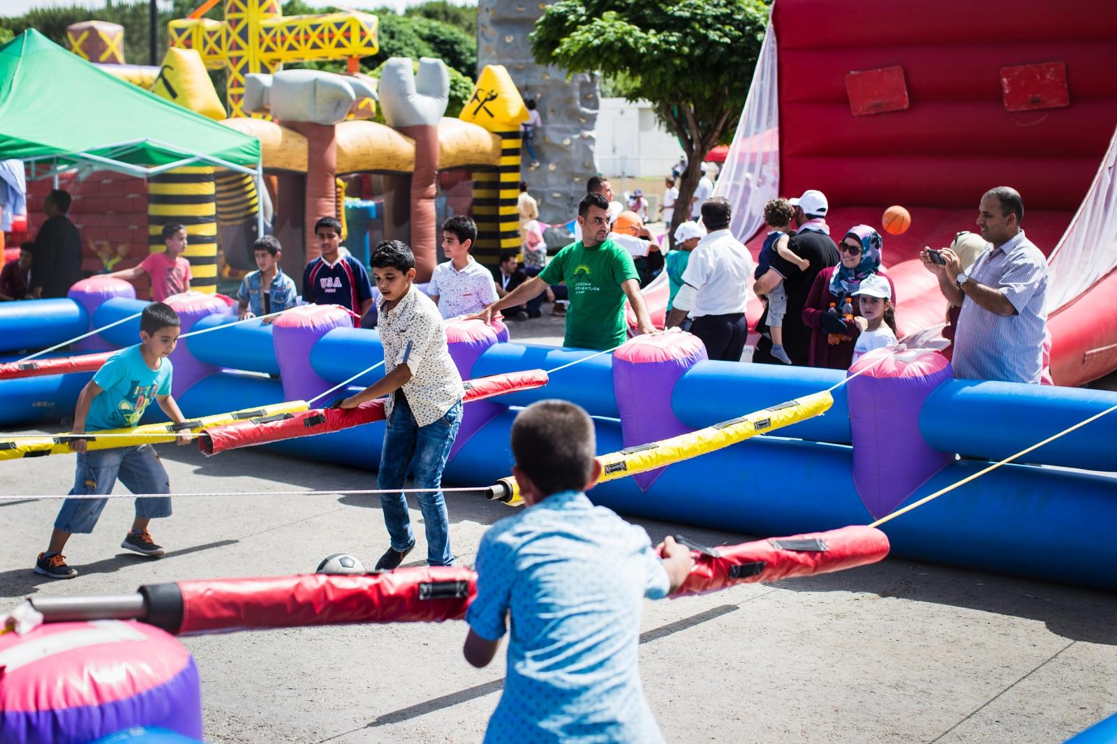 Jordanian boys play human foosball in a children's area during celebrations marking the 100th anniversary of the Great Arab Revolt in Amman, Jordan, on June 3, 2016.