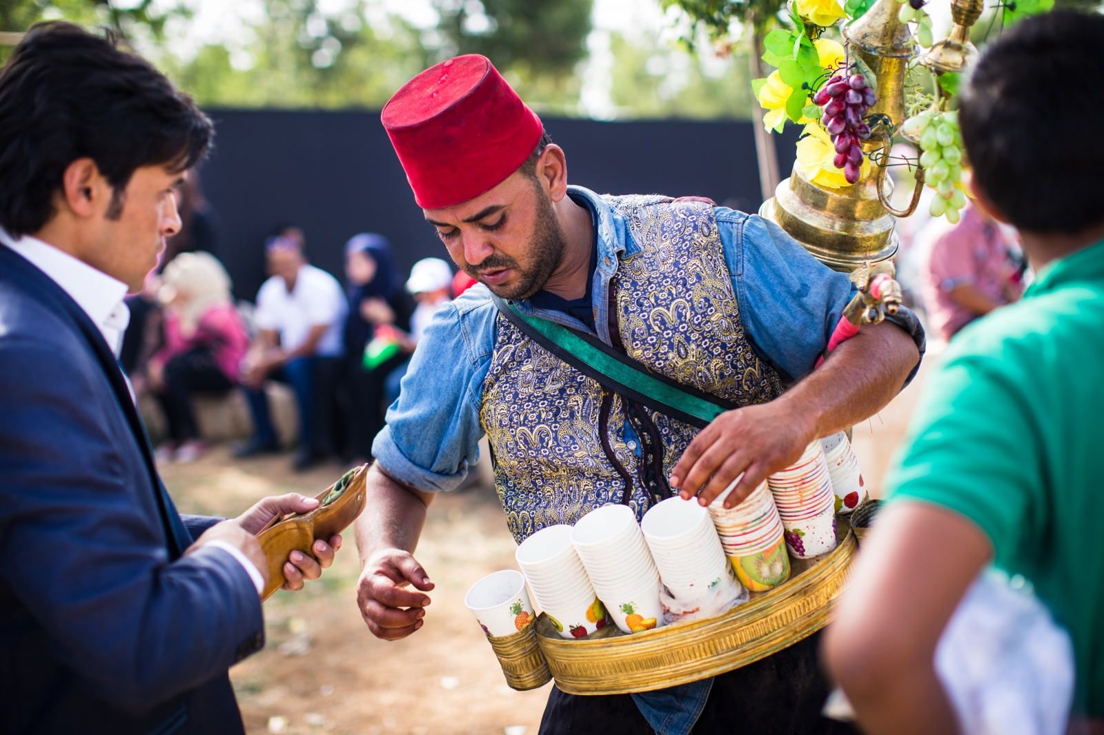A Jordanian man wearing an Ottoman-style vest and fez, pours iced hibiscus juice for people attending celebrations at King Hussein Park in Amman, Jordan, marking the centennial of the Great Arab Revolt on June 3, 2016.