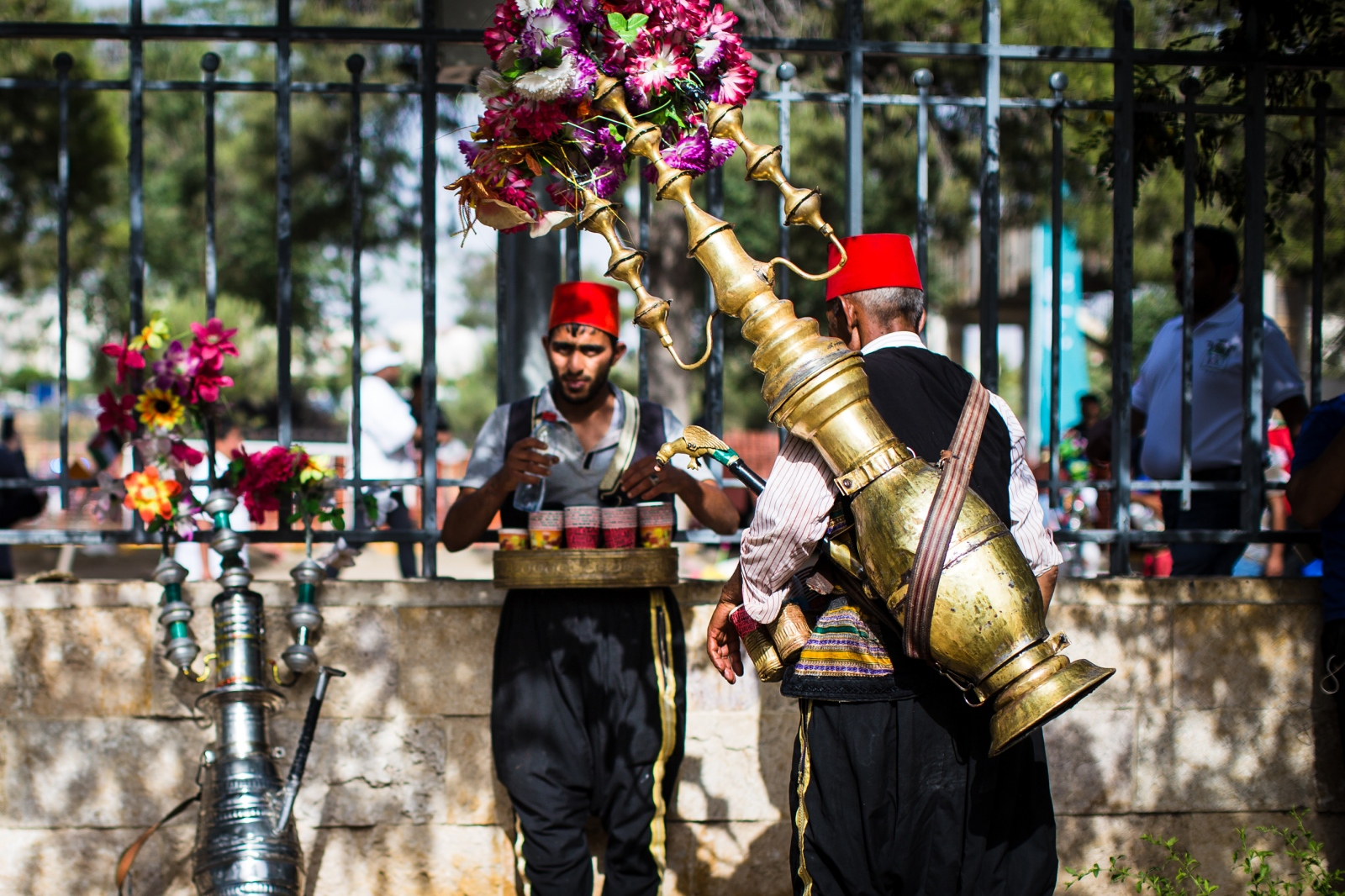 Two men selling iced hibiscus juice from a traditional gold pitcher rest in the shade to re-stock their cups. Thousands gathered at King Hussein Park in Amman, Jordan, to mark the centennial of the Great Arab Revolt on June 3, 2016.