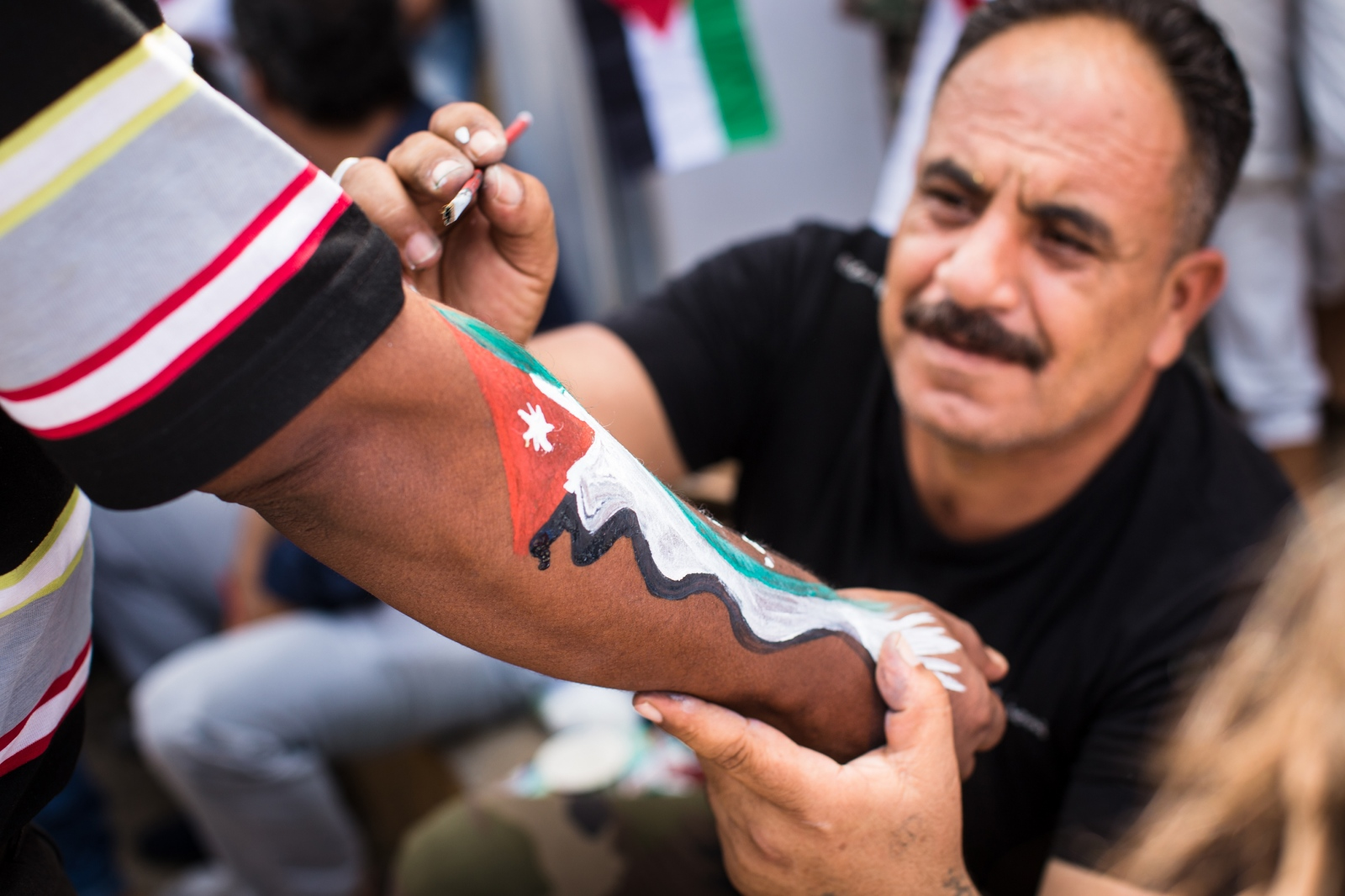 A man gets the Jordanian flag painted on his forearm at celebrations marking the centennial of the Great Arab Revolt in Amman, Jordan, on June 3, 2016.