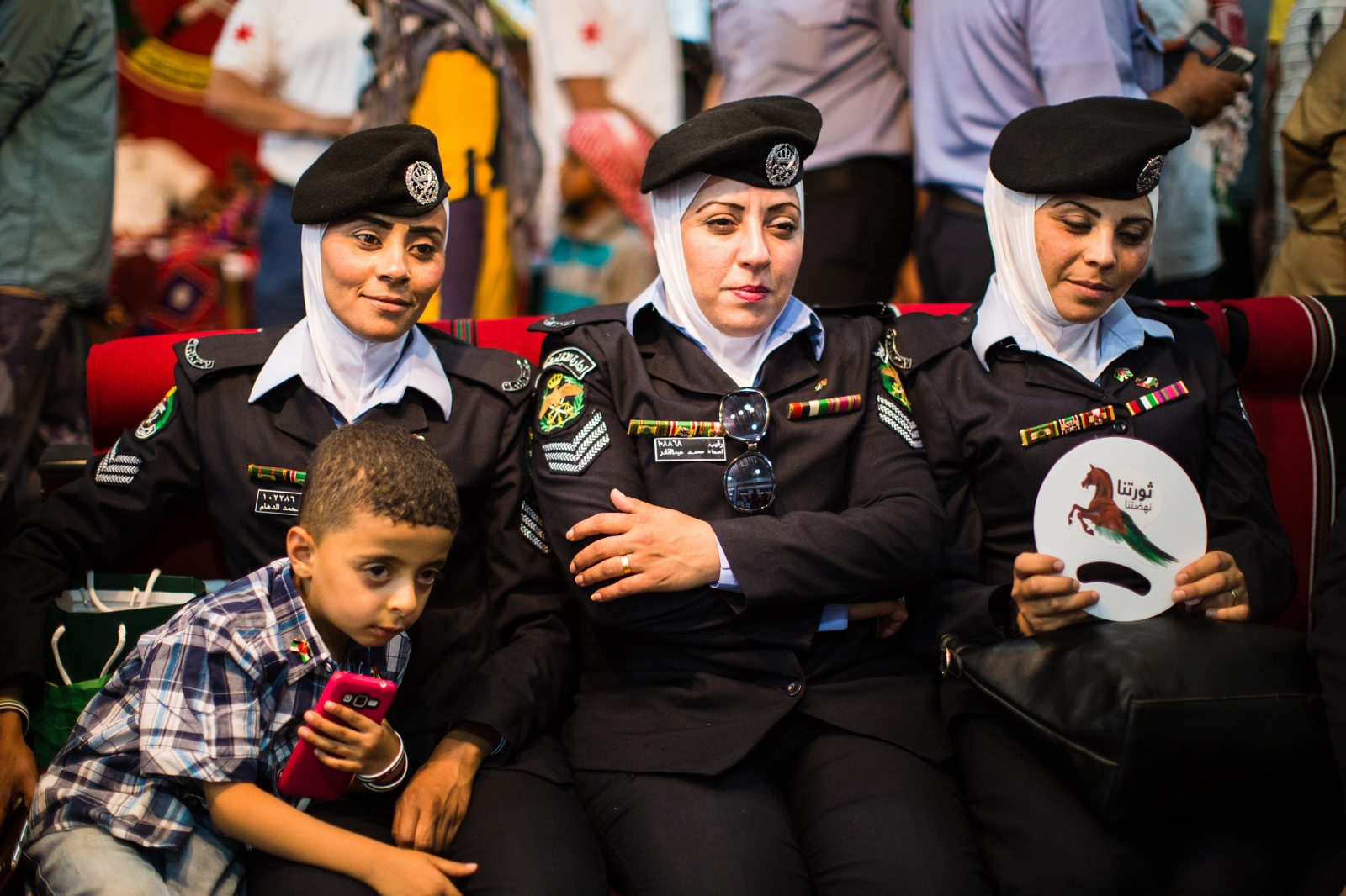 Jordanian women police officers sit with their kids at a police exhibition at a festival marking the 100th anniversary of the Great Arab Revolt in Amman, Jordan, on June 3, 2016.