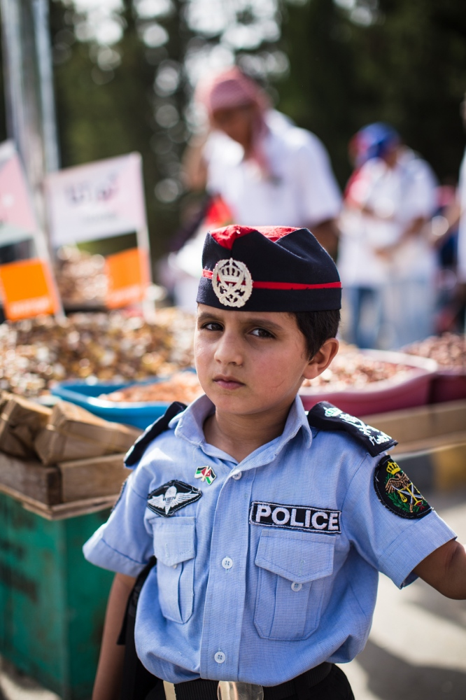 A Jordanian boy wearing a police uniform poses for a portrait outside of King Hussein Park in Amman, Jordan, at a celebration marking the 100th anniversary of the Great Arab Revolt on June 3, 2016.