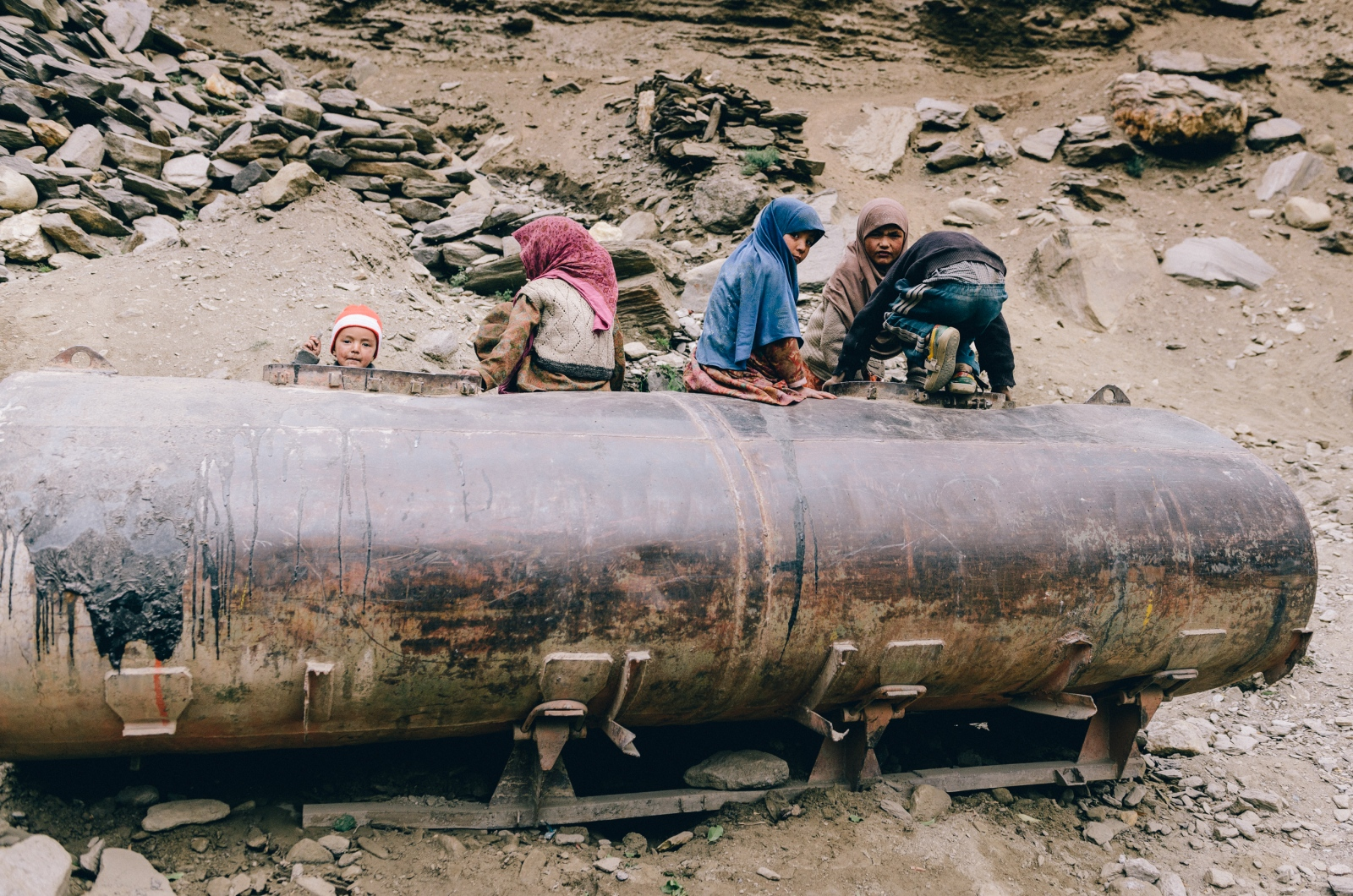 Young Kashmiri children play on an abandoned oil tank near Tongul, Kashmir.