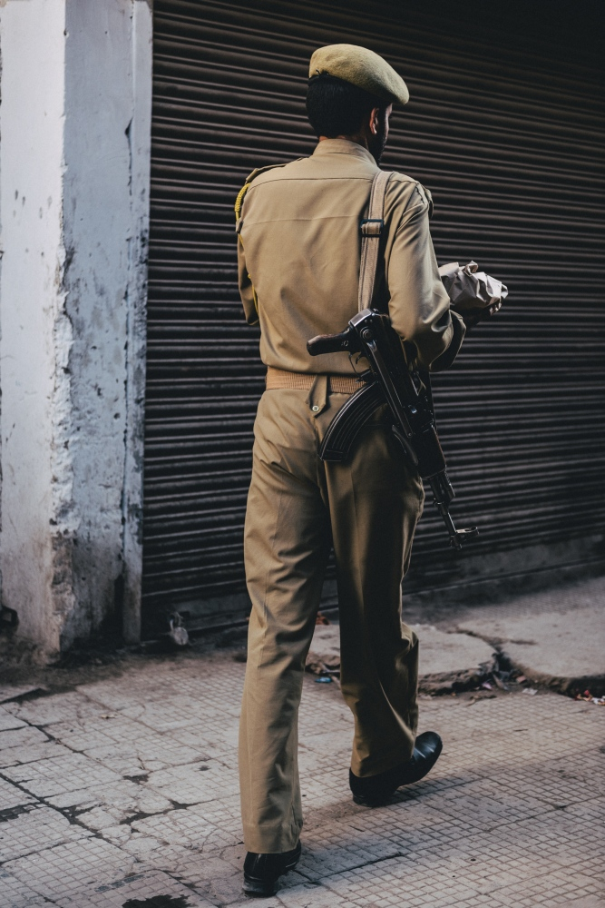 A local Ladakhi-Kashmiri policeman patrols the back alleyways of Leh with rifle slung on shoulder and lunch in hand.
