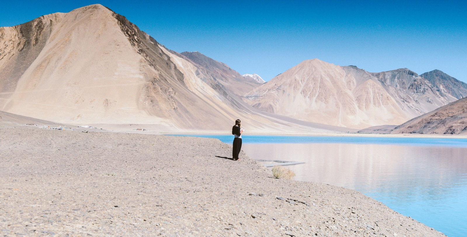 A young Israeli woman by the shore of Pangong Lake faces West towards Jerusalem for prayers on a day of Sabbat on the contested India-China border in Ladakh.