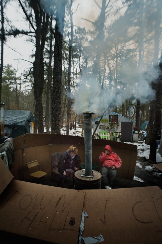 "Dawn and Bear keep warm around a homemade heater in tent City's ""town Hall"""