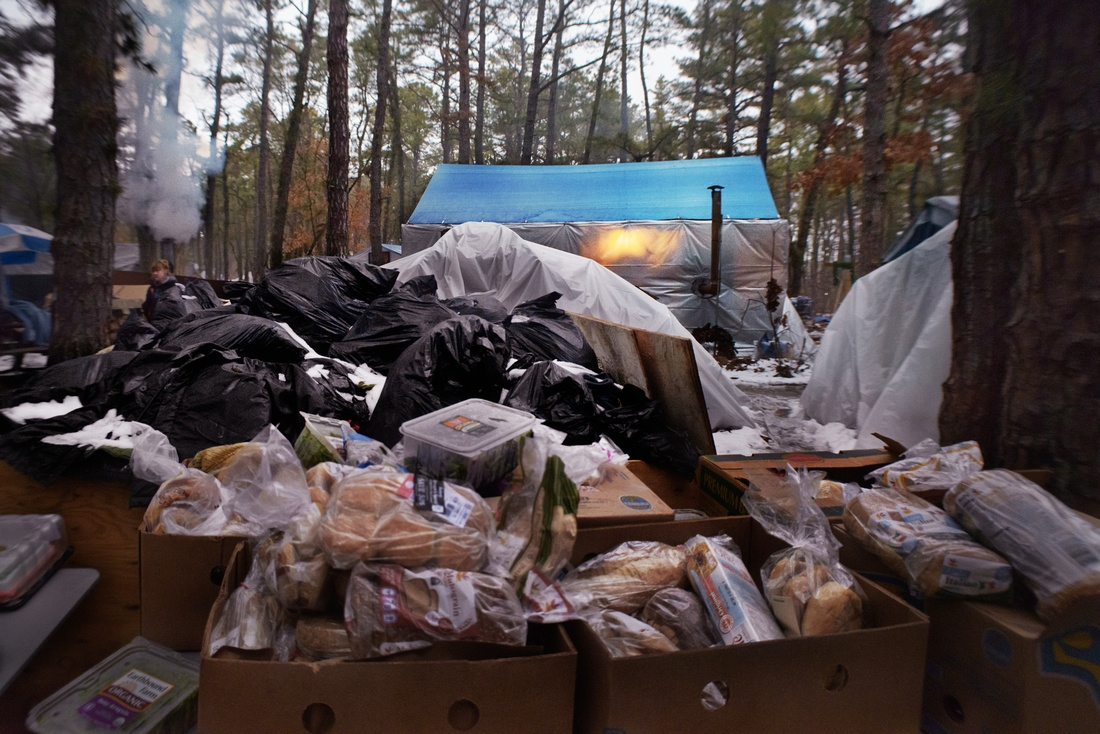 Donated food and clothes are left to rot outside of Tent City's chapel