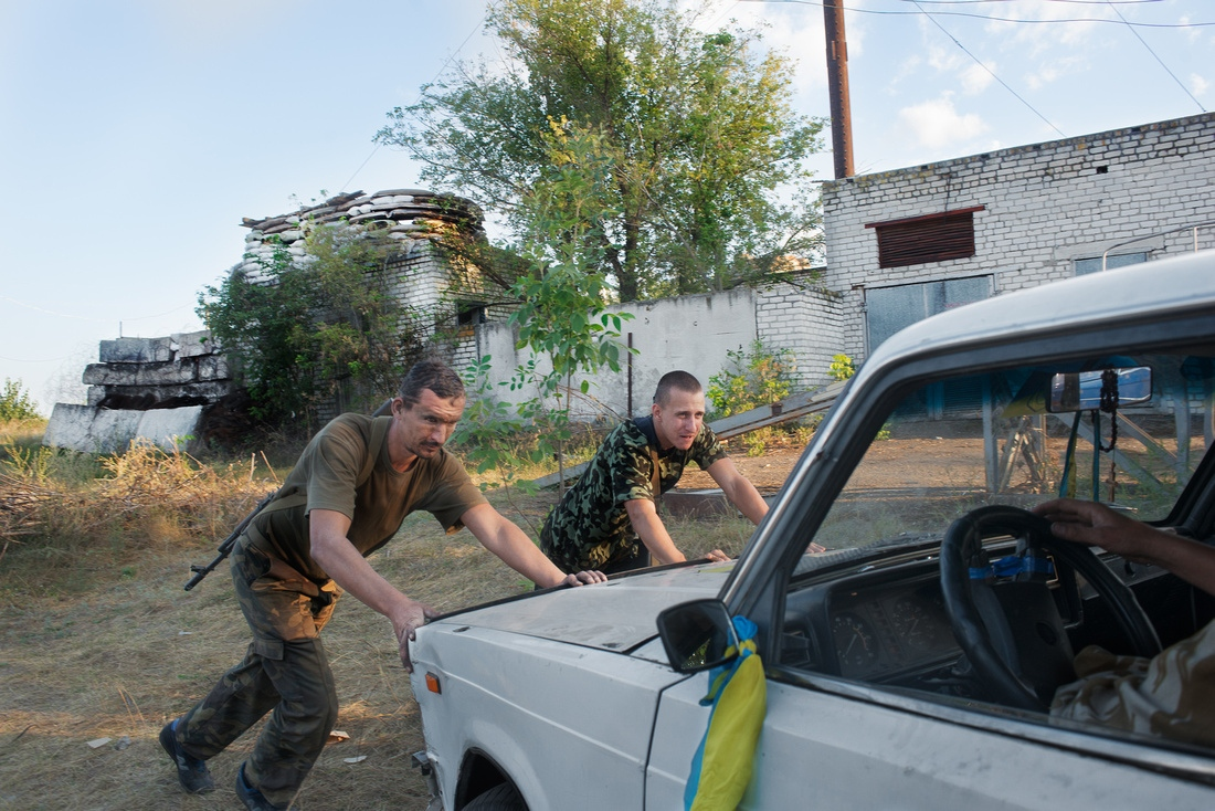 Near Luhansk, Ukraine - Volunteers with Battalion Aidar attempt to start a car used to transport troops to and fro the front. Sevaral of the men requested I ask President Obama for a few cars.
