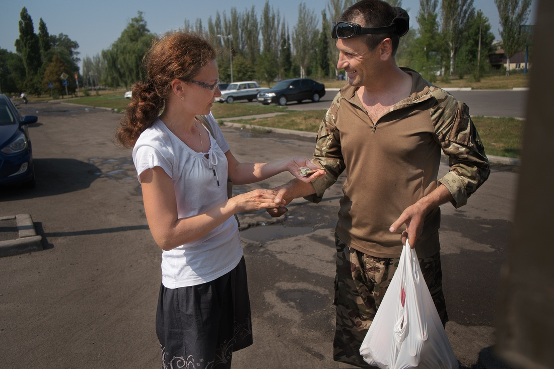 "A local woman offers ""Raven"", a driver and mechanic with Battlalion Donbas, a donation for the Battalion."