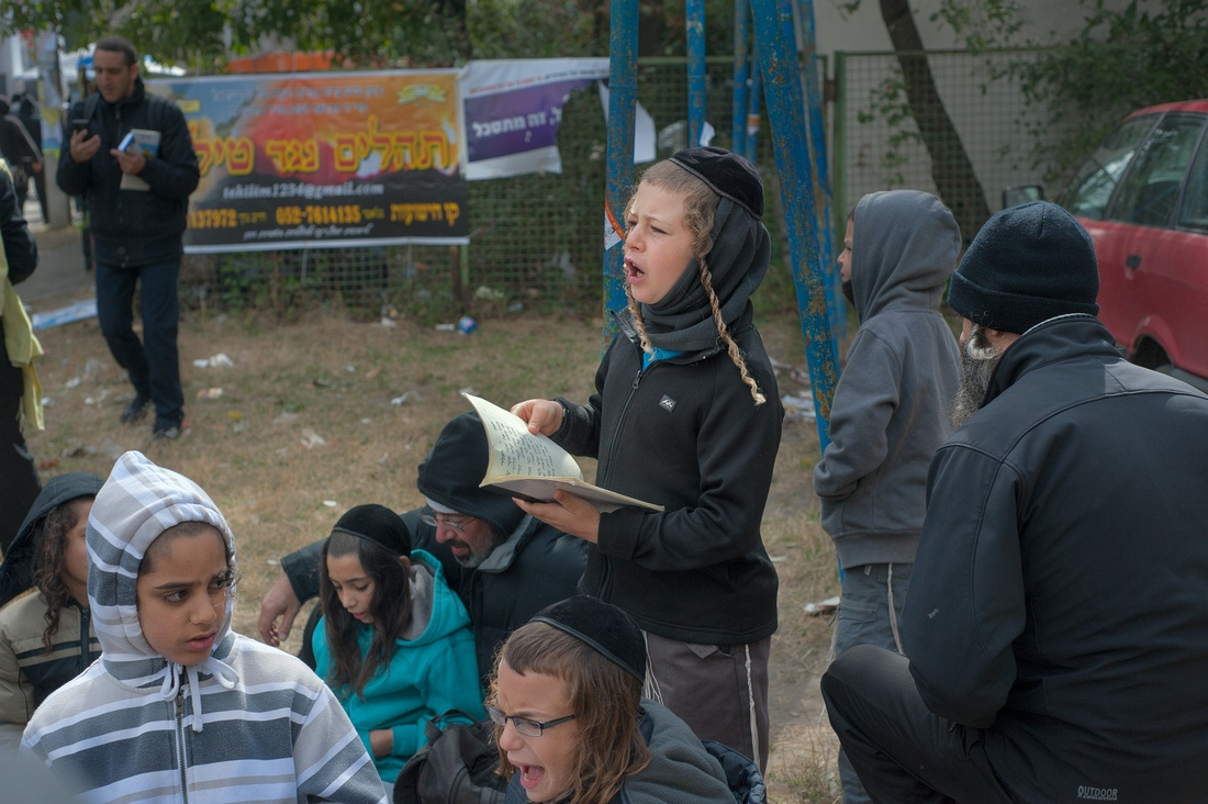 A boy recites prayers in a playground. The Uman pilgrimage becoming a father and son tradition.