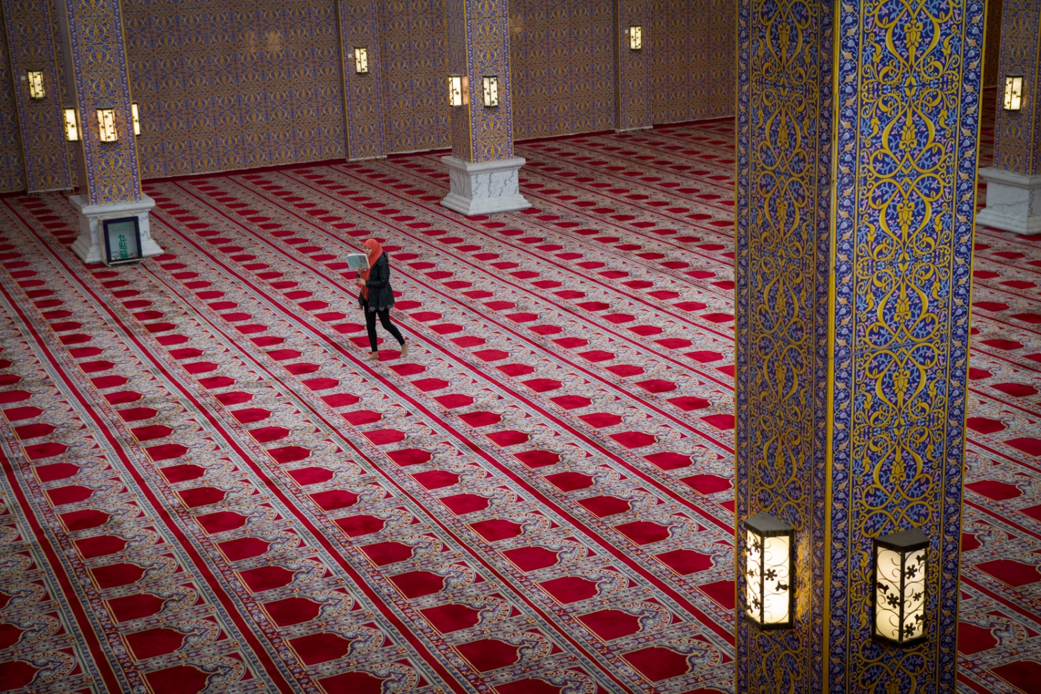 A Hui staffer chants prayers in Arabic as she walks through the main hall of the Golden Palace at the Hui Culture Park outside of Yinchuan, in the autonomous region of Ningxia.