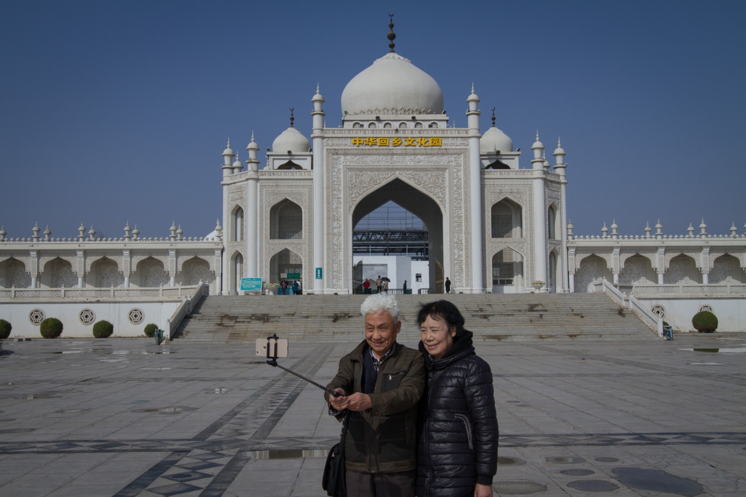 Visitors take a selfie in front of the Taj Mahal-inspired main entrance to the Hui Culture Park. The park's name is inscribed in yellow over the gates.