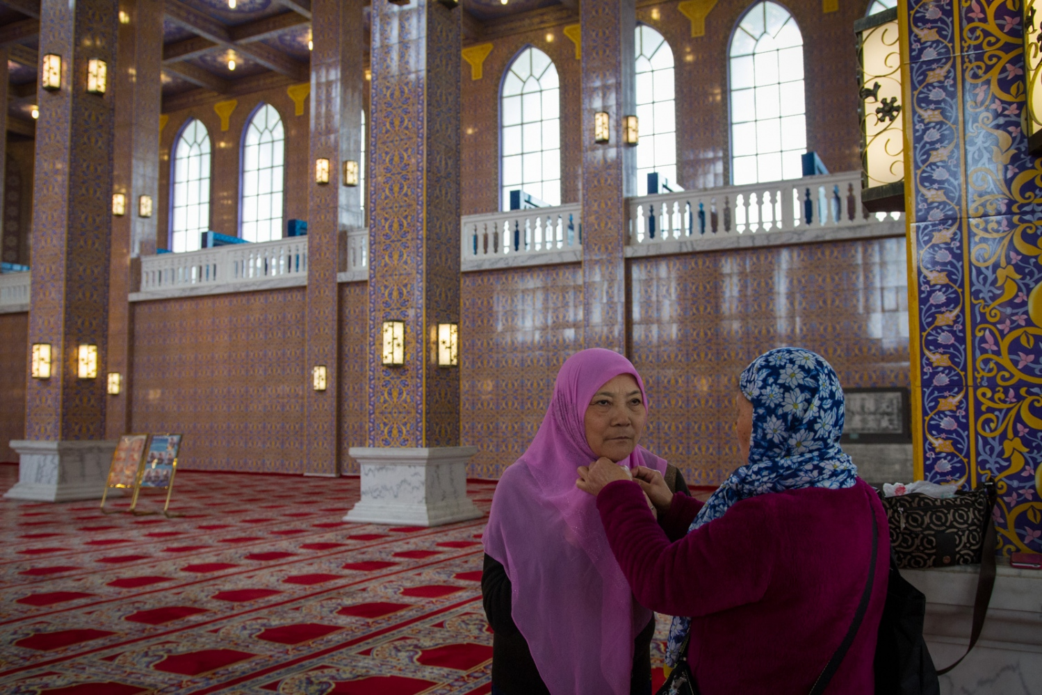 A Hui woman helps her friend to put on the headscarf in the Golden Palace where all women visitors are asked to wear headscarves. Although being Hui, the two women said they don't have to wear headscarf at home in Zhengzhou, Henan Province.