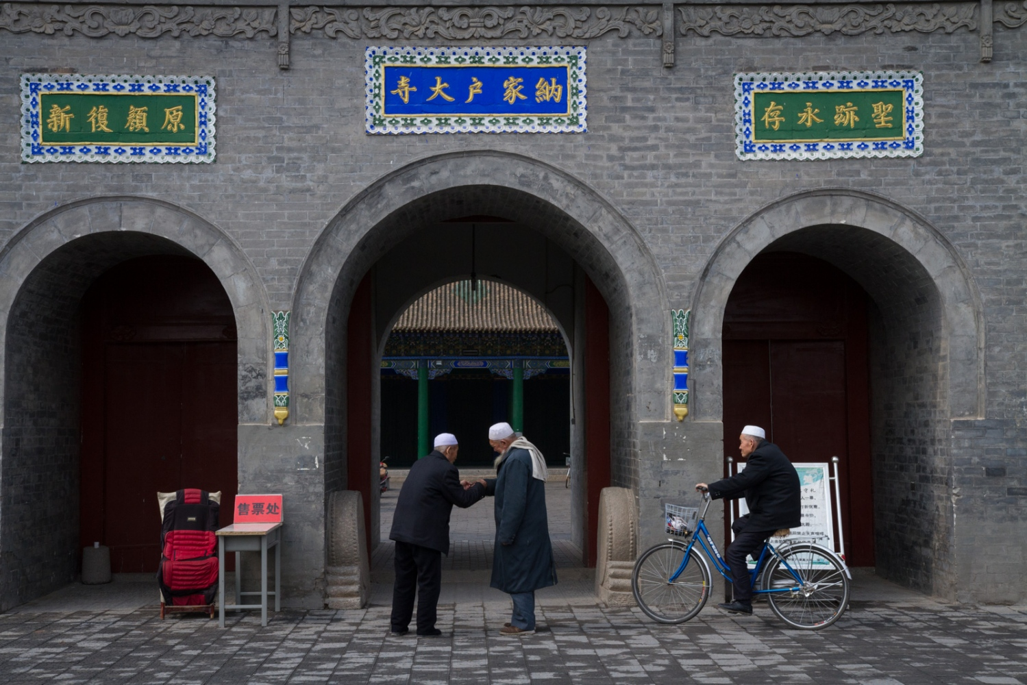 "Two Muslim Hui men stand at the gate of Najiahu Mosque talking before the prayer. The sign on the table on the left reads ""ticket."" Tourists will buy tickets here before they enter the mosque."
