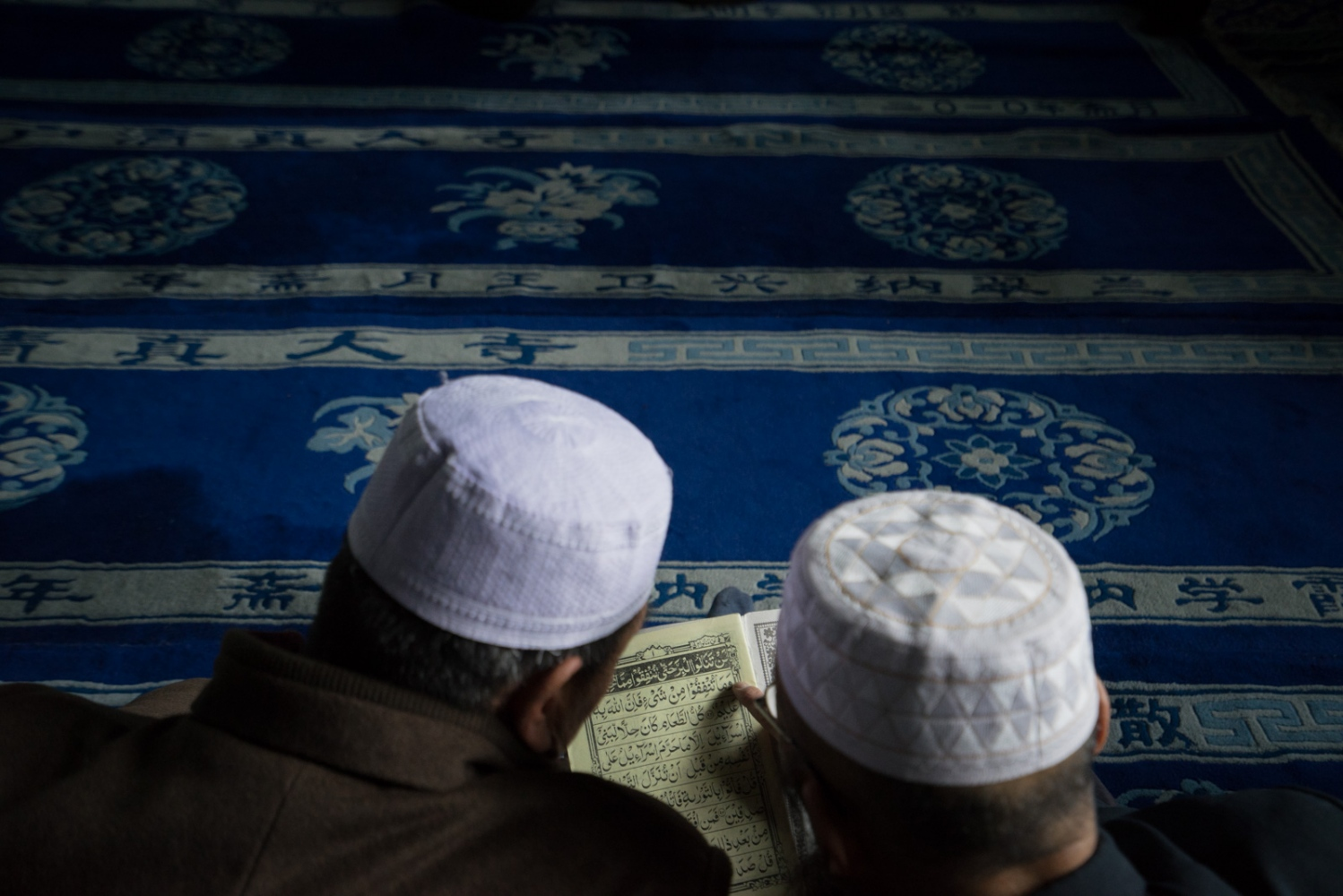 Two men sit on the floor and read a Quran together, before the prayer begins in the main prayer hall of Najiahu Mosque, March 23, 2016.