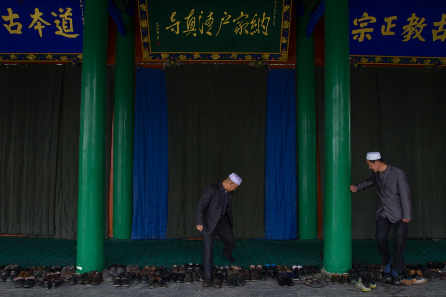 Two men leave their shoes at the entrance to the main prayer hall of Najiahu Mosque.