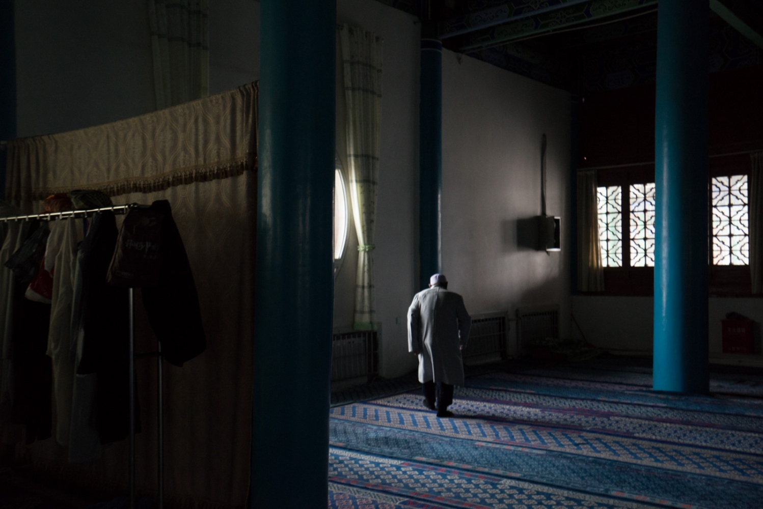 An observant man walks to the corner of the main prayer hall of Najiahu Mosque before mid-day prayer.