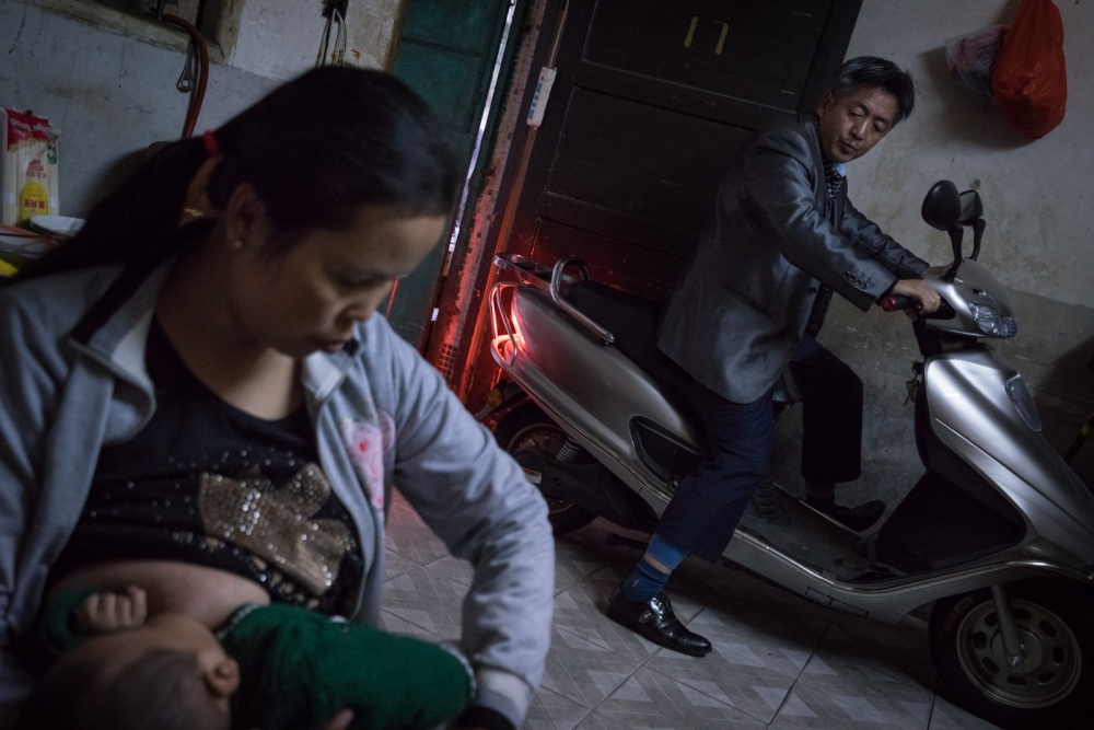 Zou arrives home after his workday on their scooter bike while Buntha feeds the baby, March 2015. At the time, Zou works as a scooter driver earning roughly 500 USD a month.