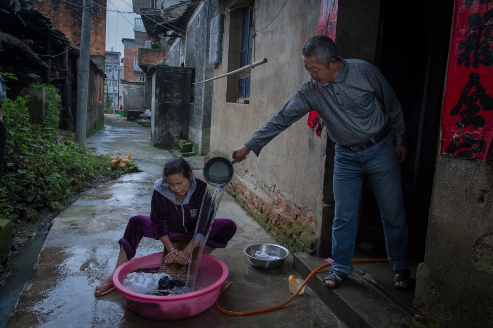 Zou helps Buntha with laundry, June 2015. In some rural parts of China, most people still wash clothes by hand.